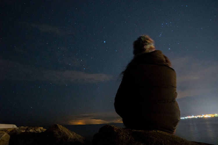 Rear view of man on sitting on cliff by sea against sky at night