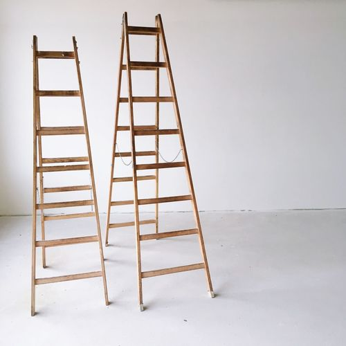 Close-up of ladders against wall