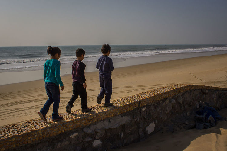 Siblings walking in a row on retaining wall at beach