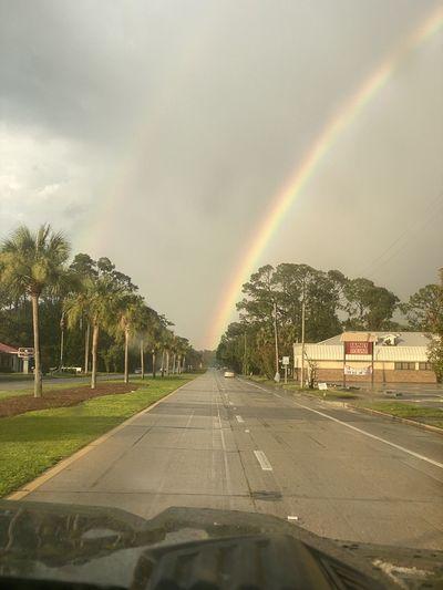 Rainbow over road in city during rainy season