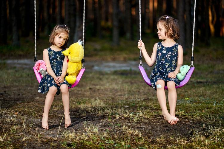Full length of sisters sitting on swings in park