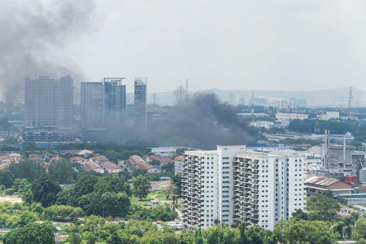Smoke amidst cityscape against sky