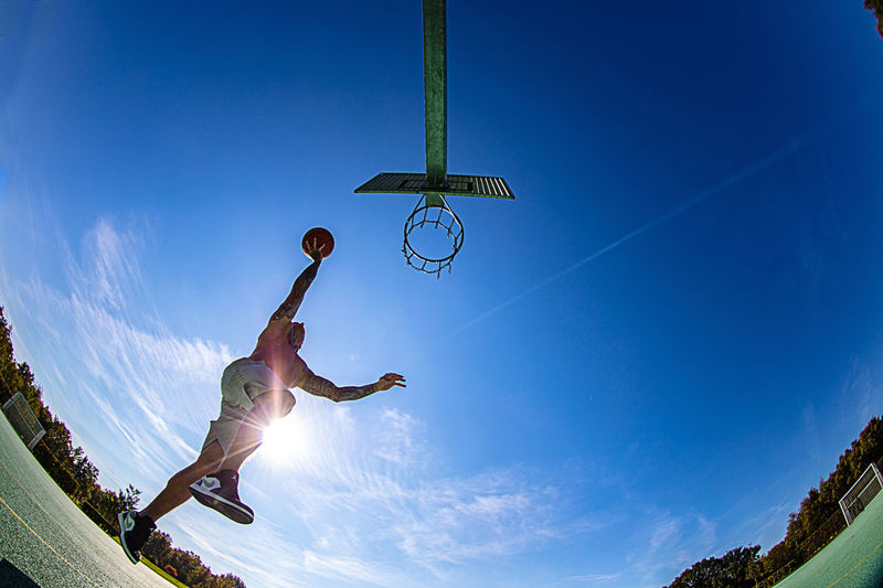 Ball Basketball Hoop Blue Day Full Length Fun Human Arm Jumping Lifestyles Low Angle View Mid-air Motion Nature One Person Outdoors Skill  Sky Sport