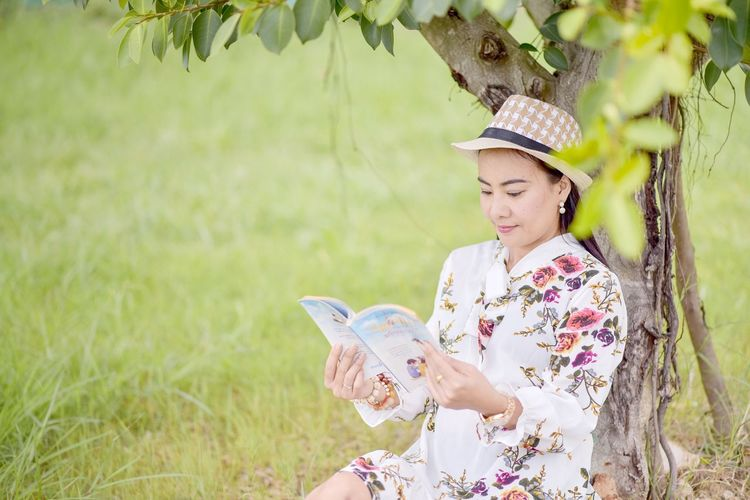 Woman Reading Book While Sitting At Park