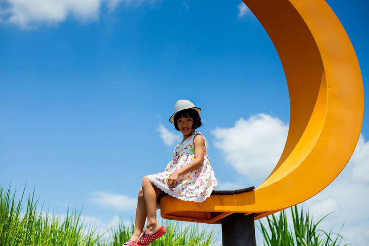 Low angle view of girl sitting on land against sky