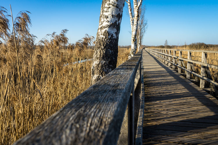 Surface level of wooden walkway on field against clear sky