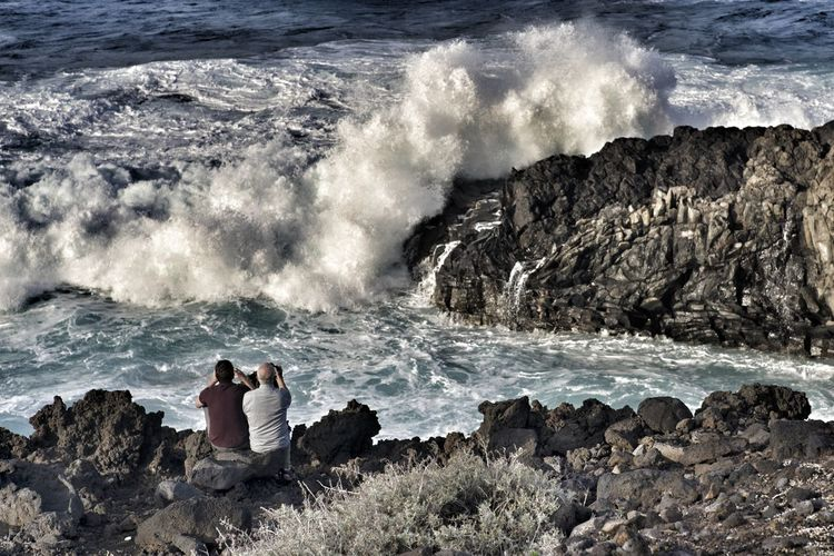 Two men photographing the ocean