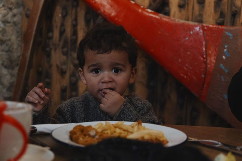 Portrait of cute baby boy eating food on table at home