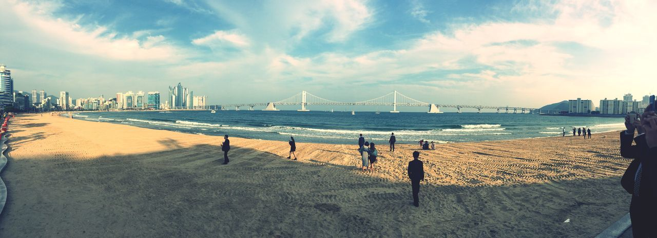 Panoramic view of people at beach with gwangandaegyo over sea against sky
