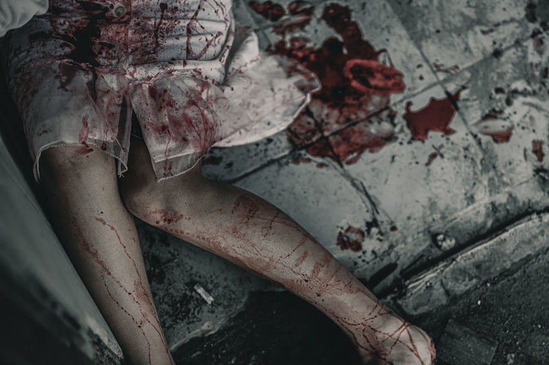 Midsection of woman with blood sitting on floor