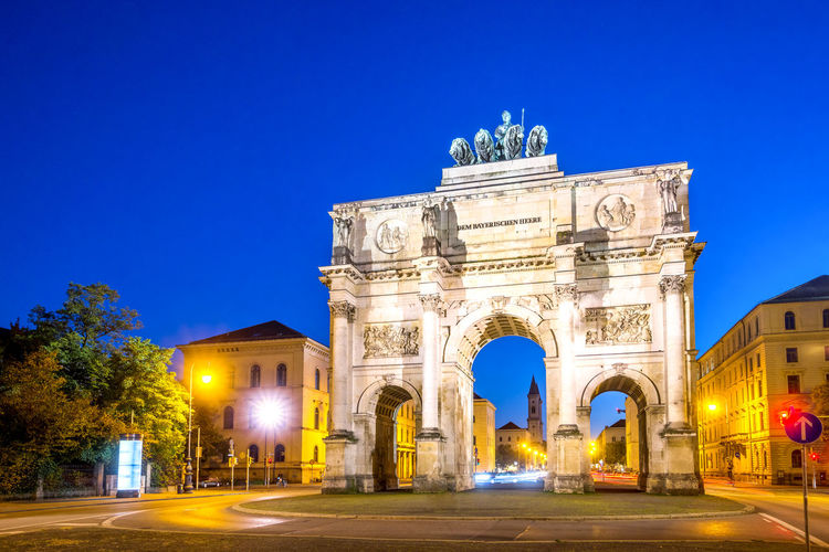 Triumphal arch and buildings in illuminated city against clear sky