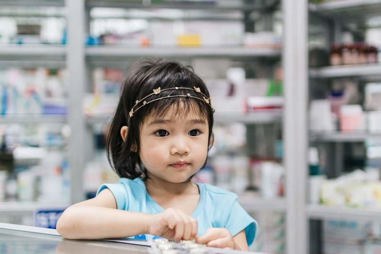Close-up cute girl wearing tiara standing at checkout in store