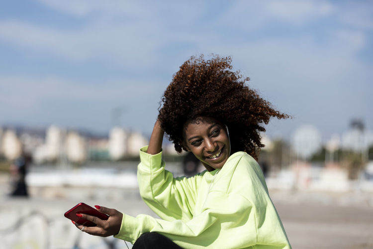 Woman with curly hair listening music while sitting at beach