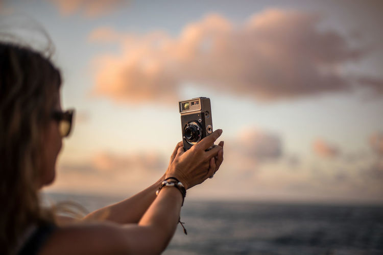 Portrait of woman photographing sea at sunset