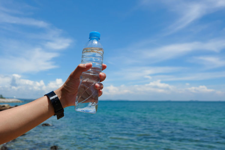Close-up of hand holding bottle by sea against sky