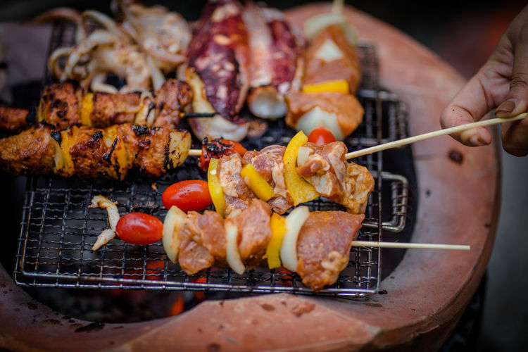 Close-up of woman holding meat on barbecue grill