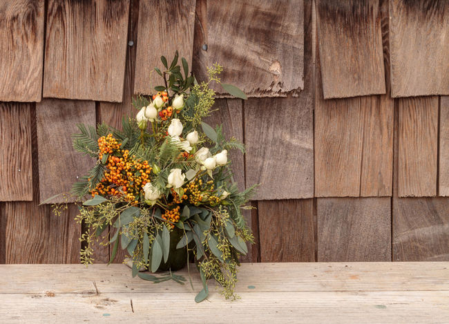 Holiday flower bouquet inside a gourd vase with red berries, green leaves and sprigs, and white roses on a rustic wood farm house background. Bouquet Day Farm Ferns Gourd Vase Holiday Nature No People Orange Berries Outdoors Plant Roses Rustic Style Thanksgiving
