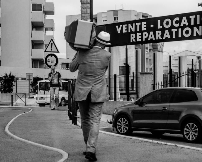Rear view of man carrying television while walking on road