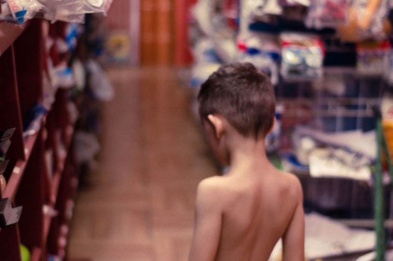 Rear view of shirtless boy by shelves