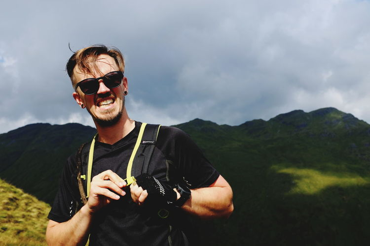 Young man wearing sunglasses against mountains against cloudy sky
