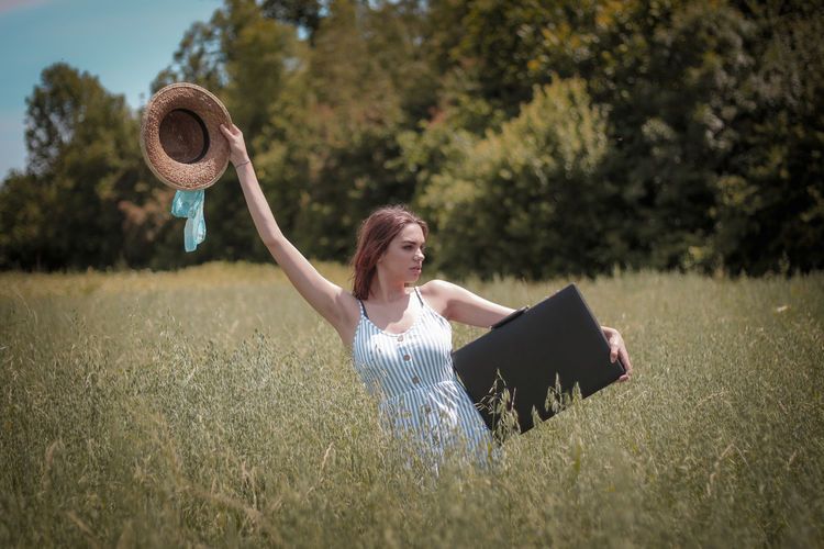 Full length of woman holding hat on field