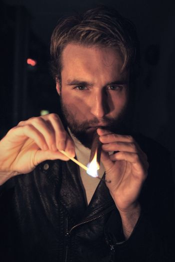 Portrait of young man lighting cigar in darkroom