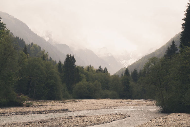 Scenic view of stream by mountains against sky