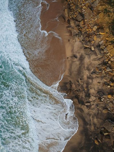 Aerial View Of Waves Splashing At Shore