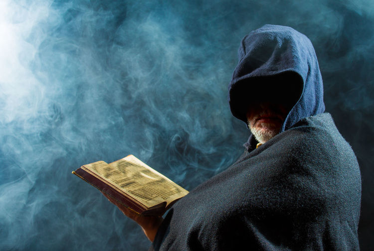 a scary man is reading in an old book Angry Cape Town Church Dark Evil Faith Halloween Old Book Cult Leader Eerie Fog Hood Hoodie Mystical Nasty Obscured Face Priest Religion Sect Sinister Smoke - Physical Structure Spooky Photo Superstition