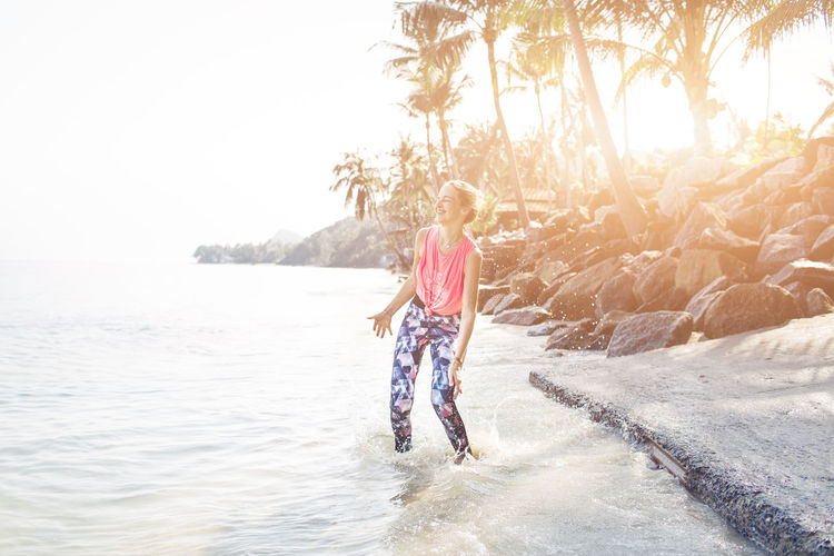 Fitness woman is jumping happy on the beach Adult Adventure Beauty In Nature Clear Sky Day Full Length Leisure Activity Lifestyles Nature One Person Outdoors People Real People Rear View Scenics Sea Sky Standing Sunlight Tree Vacations Walking Water Young Adult Young Women