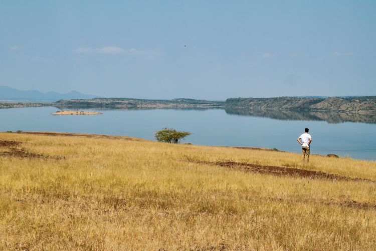 A man standing at a lake against sky at lake magadi, kenya, rift valley