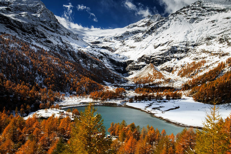 Scenic view of snowcapped mountains and lake during autumn