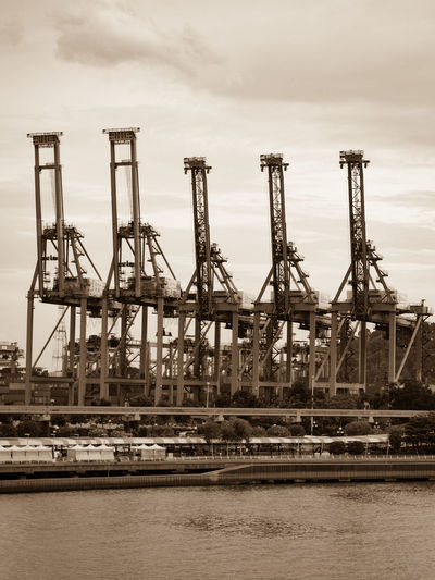 Container cranes Container Crane Architecture Business Commercial Dock Construction Equipment Container Crane - Construction Machinery Freight Transportation Harbor Industrial Equipment Industry Machinery Nautical Vessel No People Pier Sepia Shipping  Sky Transportation Water Waterfront