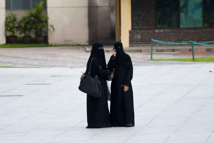 Women in burka standing on road