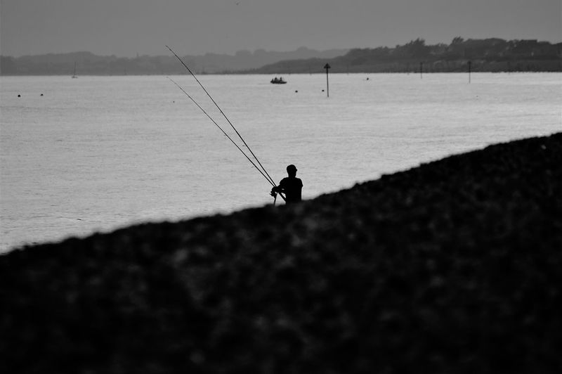 Sea Water Beach Pebble Beach vanishing point Rippled Ocean Fishing Fishing Rod Fisherman One Person person Man Fishing Reel Vanilla Filter Blackandwhite Rod Leisure Activity Nature Beauty In Nature Scenics - Nature Tranquility Tranquil Scene Real People Young Adult Young Man Fish Catch Sport Pastime Activity Lifestyles Sky Clear Sky Copy Space Patience Land Day Outdoors Surface Level Selective Focus Rear View Sunlight Silhouette Shadow