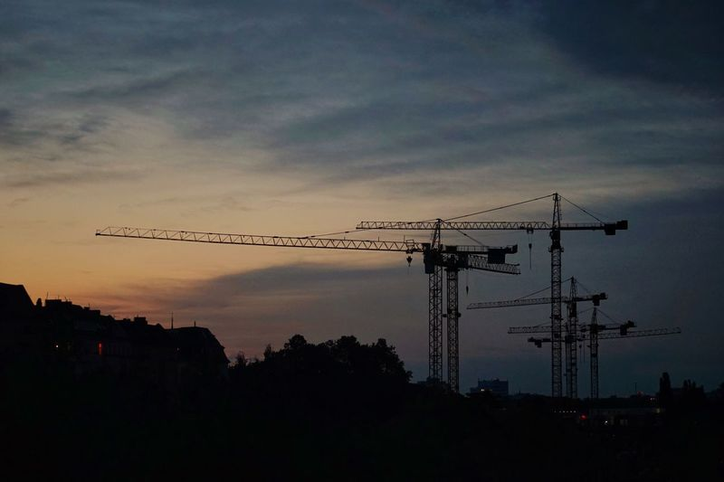 Silhouette cranes against sky at sunset