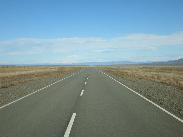 Road Sky Landscape Environment Transportation Sign Symbol Direction Scenics - Nature Diminishing Perspective Tranquil Scene Land Road Marking Day Nature vanishing point The Way Forward Tranquility Non-urban Scene Horizon Over Land No People Outdoors Dividing Line Long Arid Climate