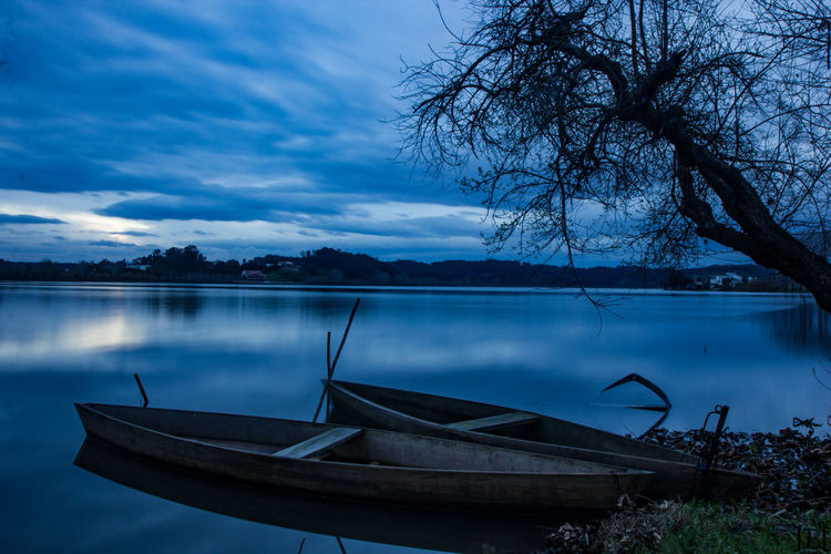 Beauty In Nature Blue Day Floating On Water Gondola - Traditional Boat Lake Lakeshore Moored Nature Nautical Vessel No People Outdoors Reflection Scenics Sky Tranquil Scene Tranquility Travel Destinations Tree Water