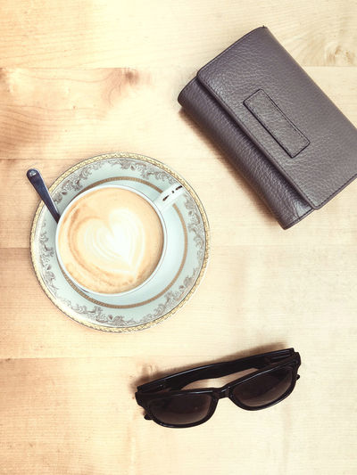 High angle view of coffee with wallet and sunglasses on table