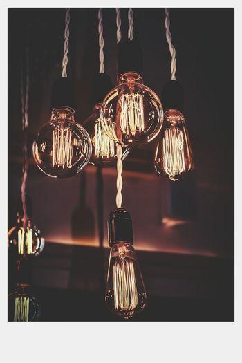Close-up of illuminated lighting equipment hanging against black background