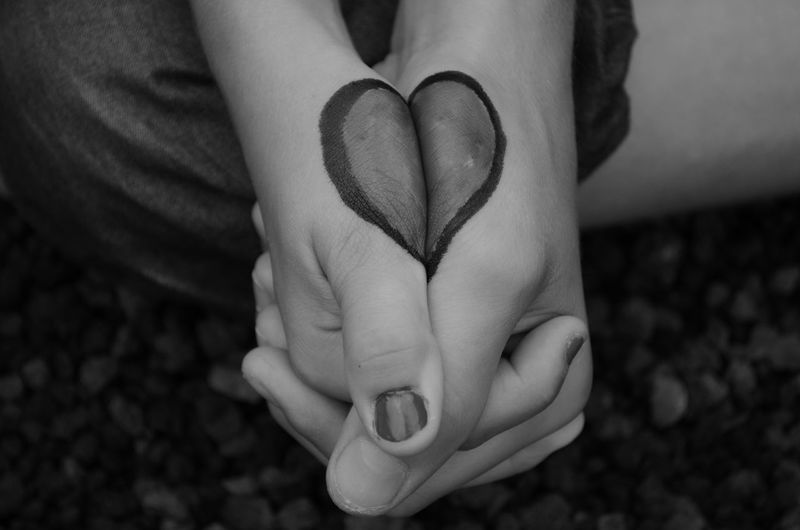 Midsection of person with heart shape made on hands clasped