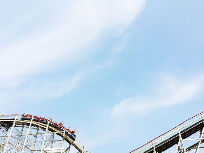 People on rollercoaster against sky