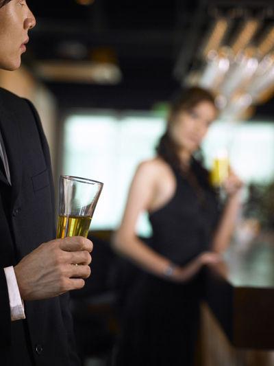 Young Businessman Drinking At Bar