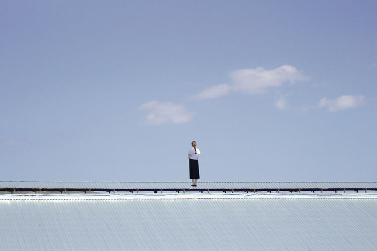 Rear view of woman standing against sky on roof