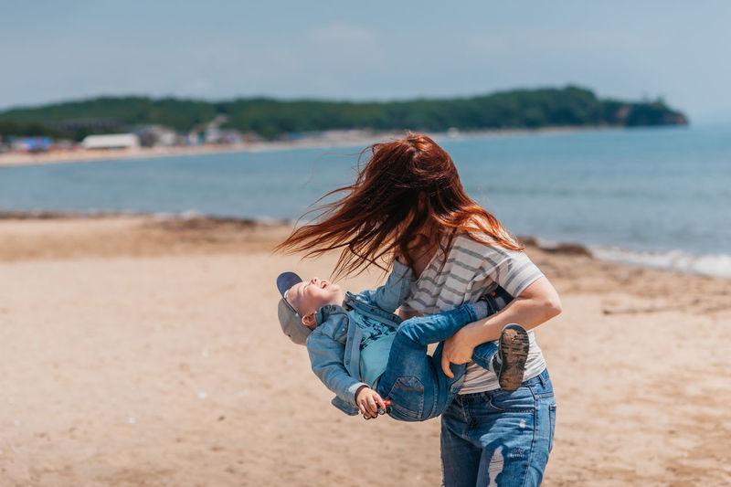 Woman holding umbrella at beach