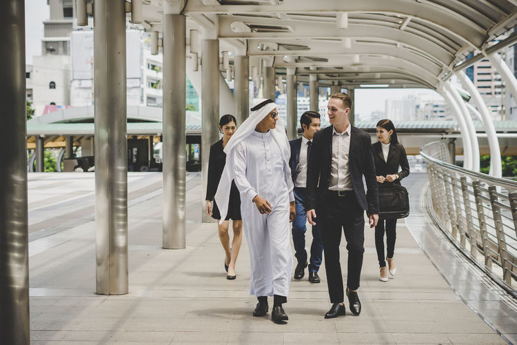 Business People Talking While Walking On Footbridge In City