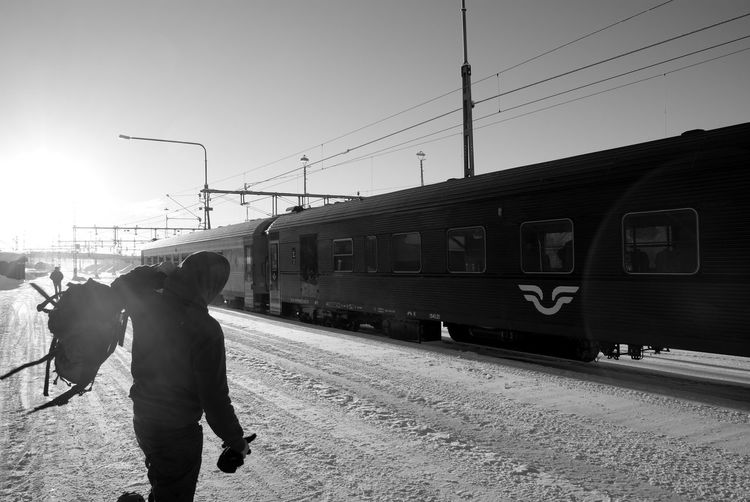 Man In Front Of Train On Snowy Landscape Against Clear Sky