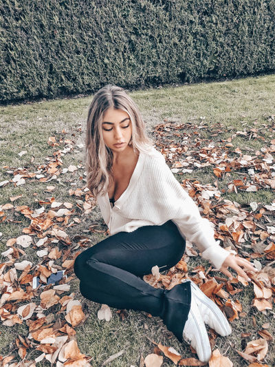 Beautiful young woman sitting on field during autumn