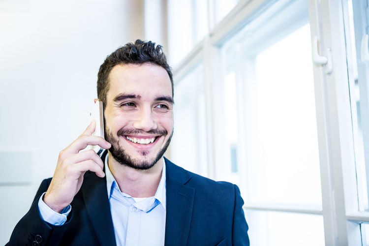 Business team in modern office environment, Adult Adults Only Beard Businessman Calling Cellphone Communication Connection Front View Happiness Headshot Mobile Mobile Phone One Man Only One Person One Young Man Only Only Men Portable Information Device Smart Phone Smiling Talking Using Phone Wireless Technology Young Adult Young Men