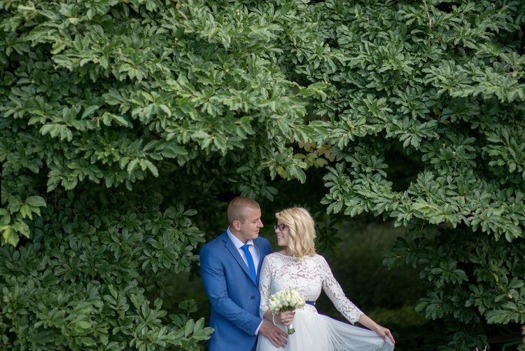 Bridal couple looking at each other while standing amidst tree branches at park